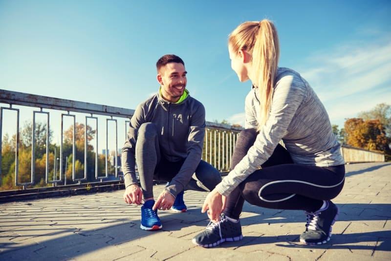lächelndes Paar binden ihre Schuhe auf der Straße