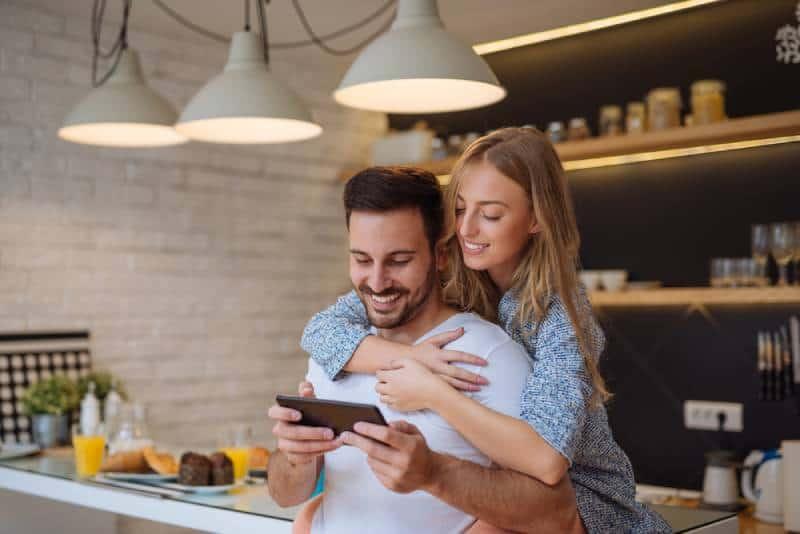 lächelndes Paar, das Telefon in der Küche betrachtet