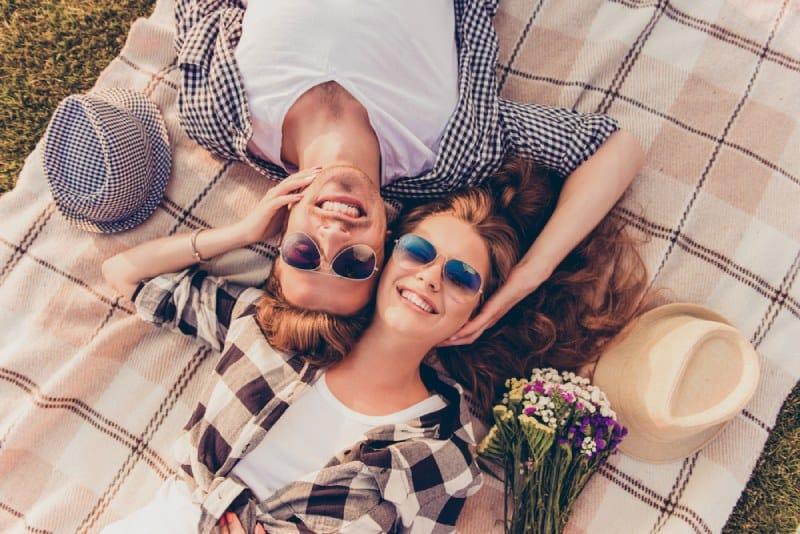 lächelndes Paar, das draußen auf einem leeren in der Natur liegt