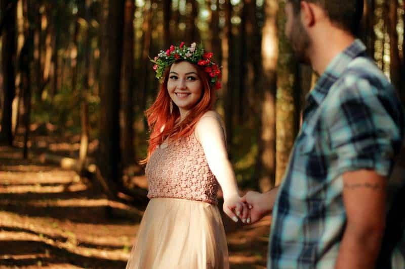 lächelndes Paar, das ihre Hände nahe Baum hält