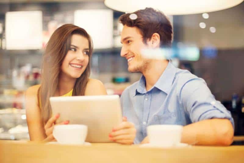 lächelndes Paar, das im Café sitzt und sich ansieht