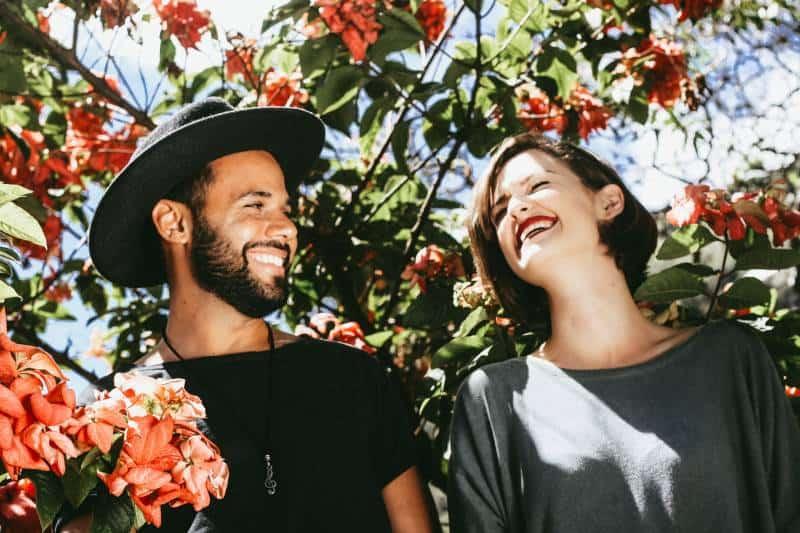 lächelndes Paar umgeben von den Blumen