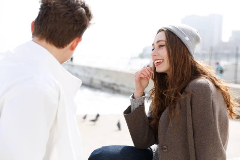 lächelndes junges Paar, das draußen sitzt und spricht