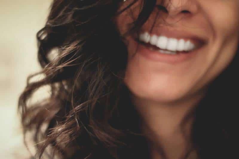 lange schwarzhaarige Frau lächelnd