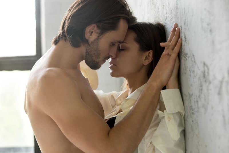 leidenschaftliche Männer küssen eine Frau
