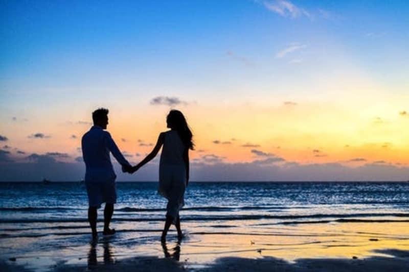 muškarac i žena koji hodaju plažom