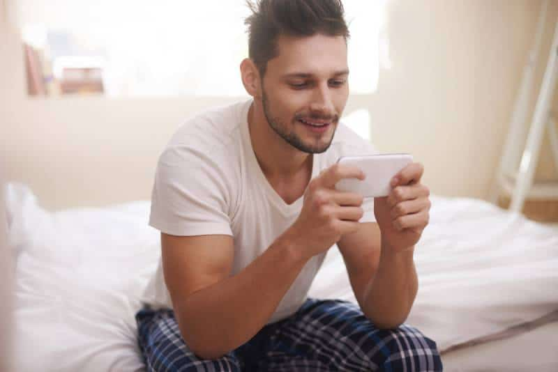 man sitting and typing on his phone in the morning