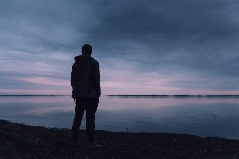 Mann am See stehen