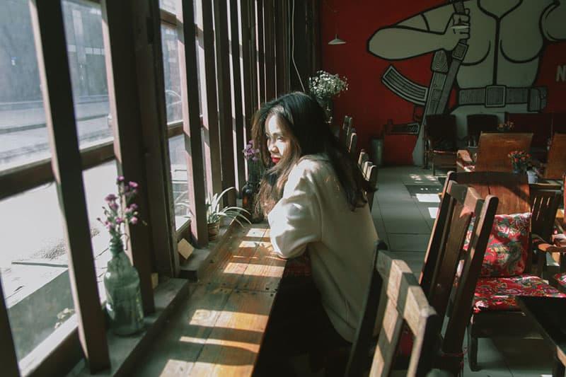 nachdenkliche Frau, die an den Fenstern am Kaffee sitzt