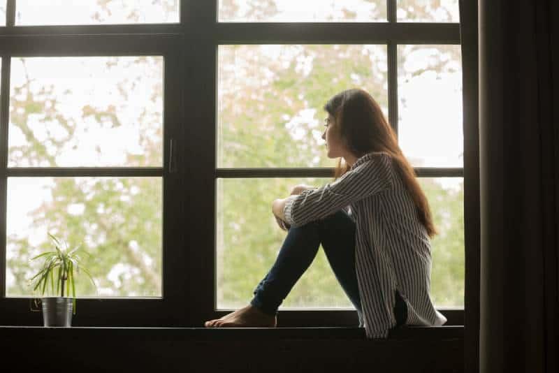 nachdenkliche Frau, die nahe Fenster zu Hause sitzt