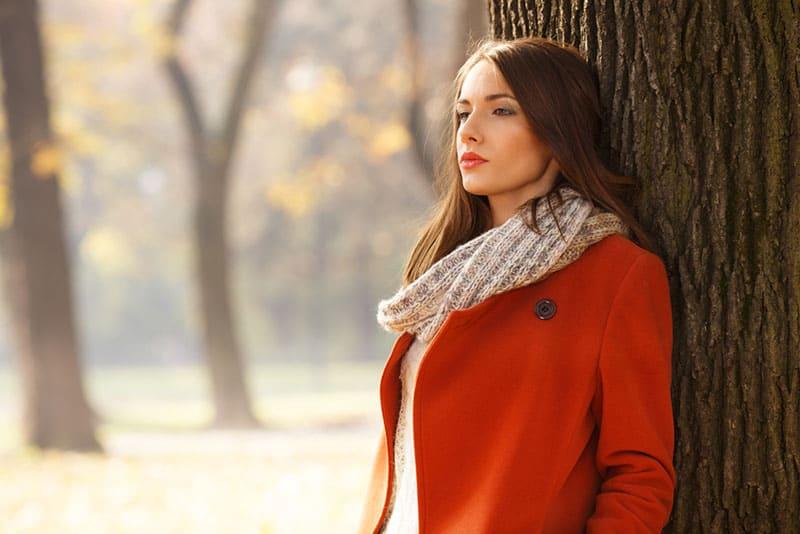 nette Frau im roten Mantel, die am Baum steht