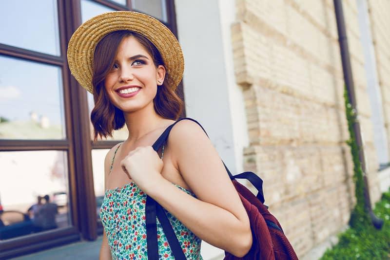 nette Frau mit roten Haaren, die einen Rucksack trägt