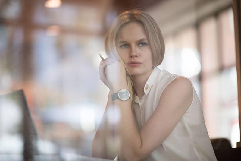 nette blonde Frau, die im Büro denkt