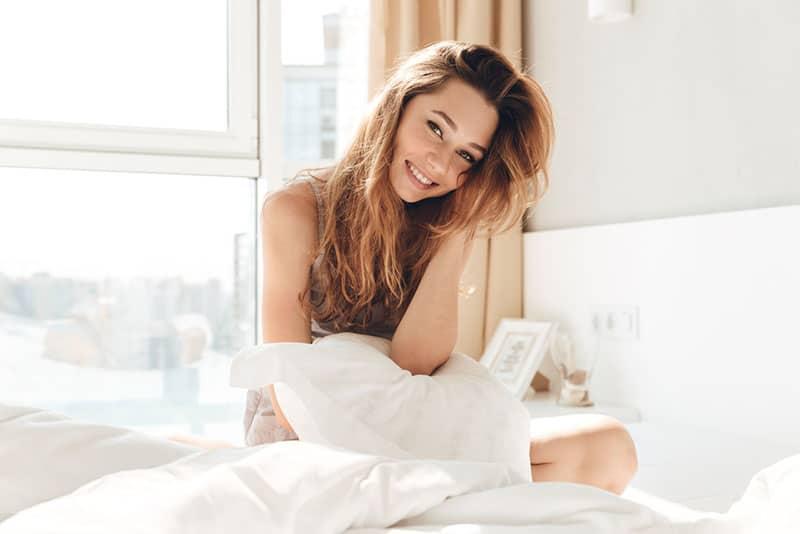 positive Frau sitzt auf dem Bett