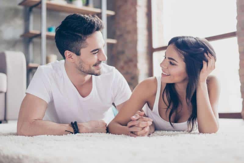 romantisches Paar, das zu Hause auf dem gemütlichen Teppich liegt