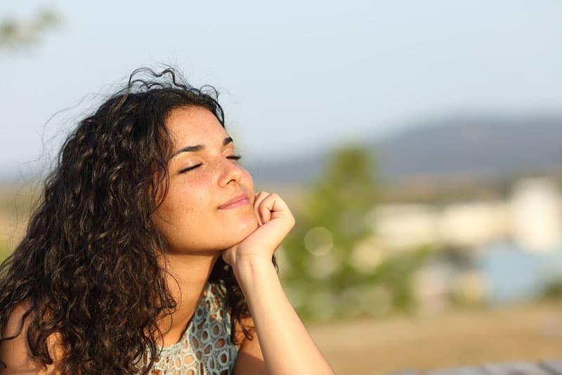 ruhige glückliche Frau mit geschlossenen Augen auf der Sonne