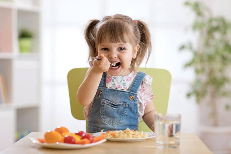 süßes kleines Mädchen, das gesundes Essen isst