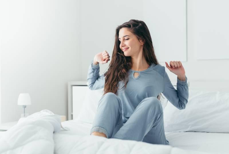 schöne Frau, die in ihrem Bett im Schlafzimmer aufwacht