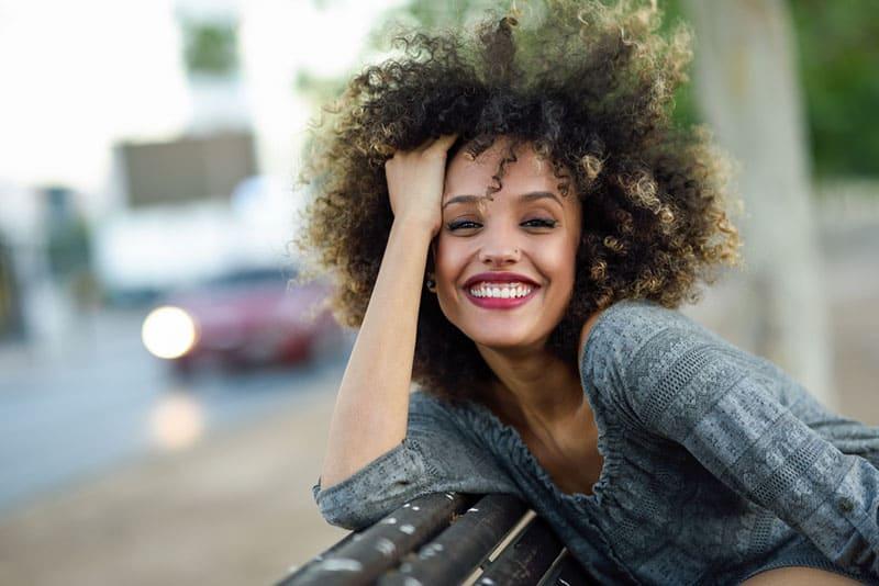 schöne Frau mit dem lockigen Haar, das auf Bank sitzt