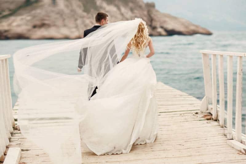 schöne Hochzeitspaar Braut und Bräutigam am Hochzeitstag im Freien am Ozeanstrand