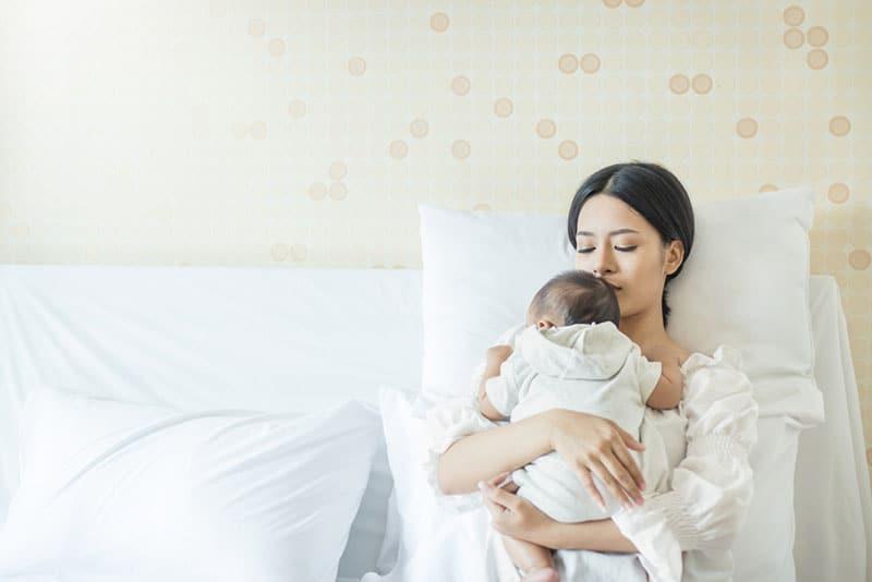 schöne Mutter hält ihr Baby