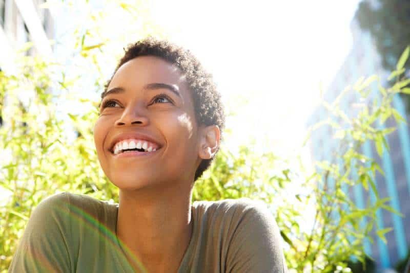 schöne junge schwarze Frau, die draußen lächelt