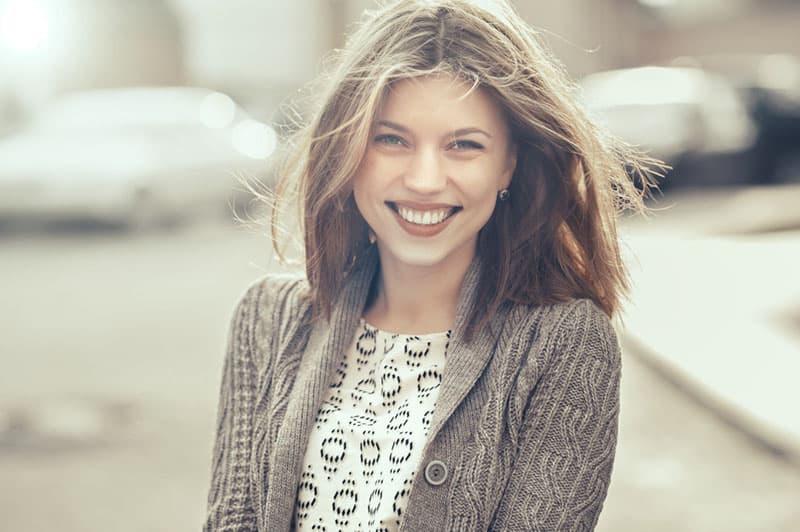 schöne lächelnde Frau, die an der Kamera aufwirft