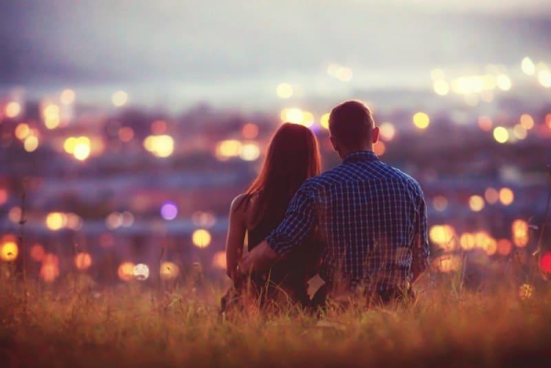 schönes Paar beobachtet Nachtstadt vom Hügel