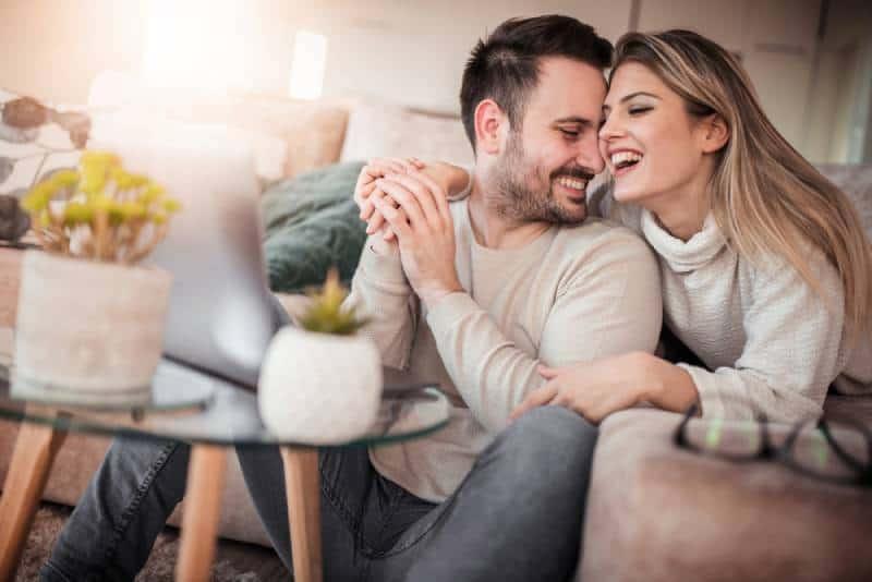 schönes Paar, das im Wohnzimmer lächelt