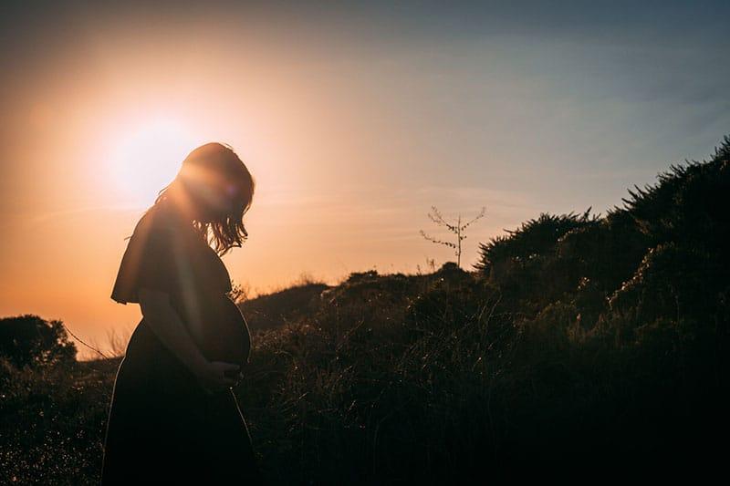 schwangere Frau, die in der Natur steht