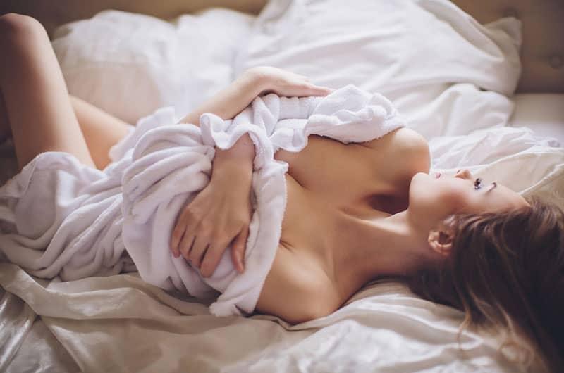 sexy Frau im Bademantel auf dem Bett