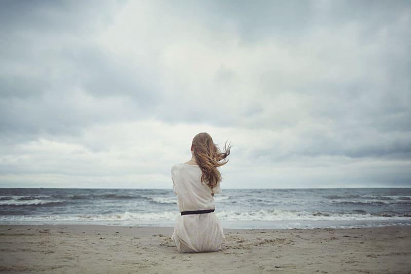 sinnliches Mädchen, das am Strand sitzt