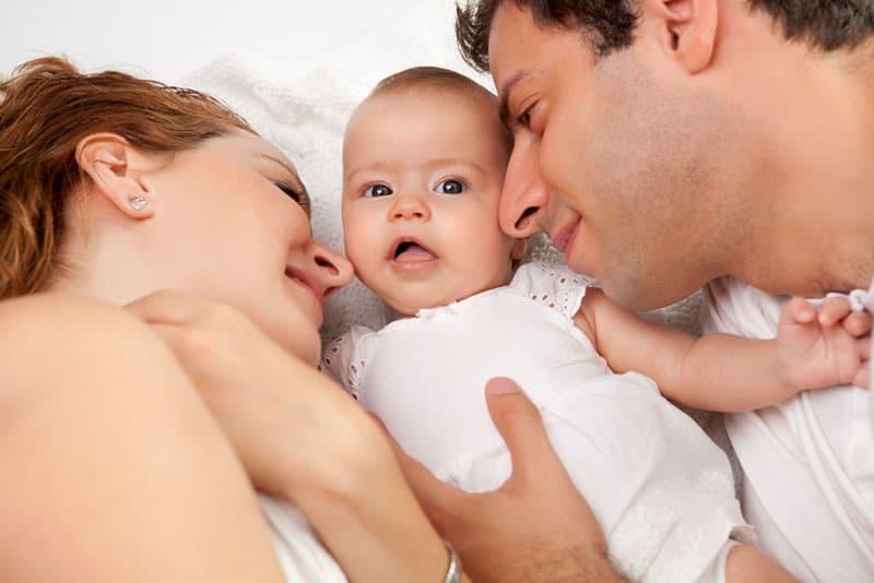 stolze Eltern, die mit ihrem Baby liegen
