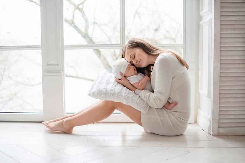 stolze Mutter umarmt ihr neugeborenes Baby