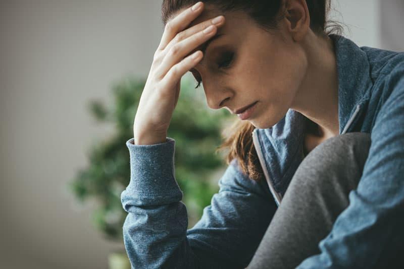 traurige Frau, die Hand auf ihrem Kopf hält