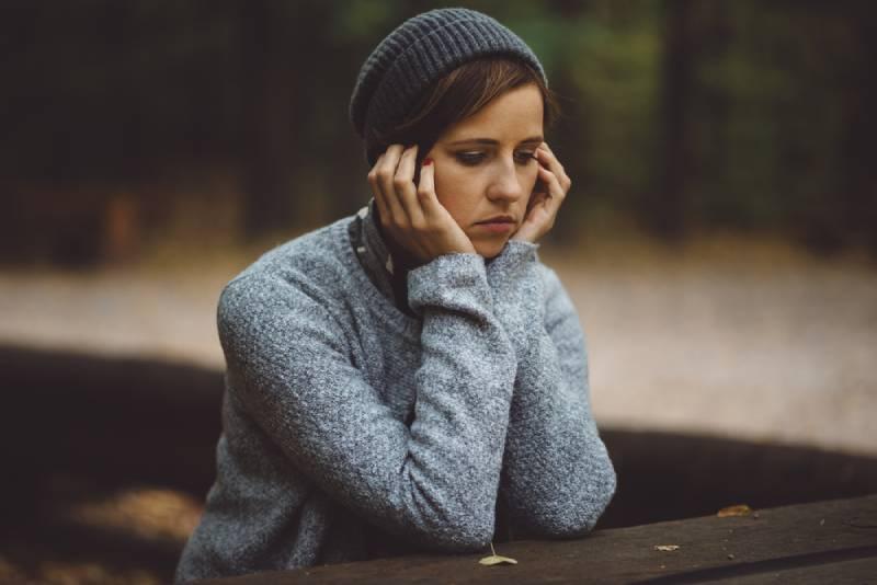 traurige Frau, die allein im Wald sitzt