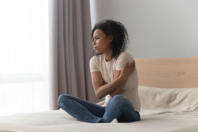 traurige Frau, die allein zu Hause im Bett sitzt