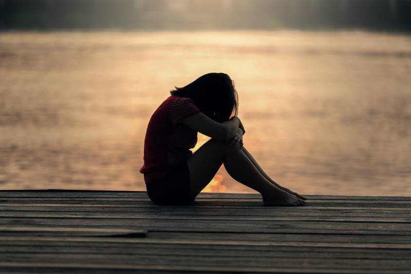 traurige Frau, die am Holz vor Körperwasser sitzt