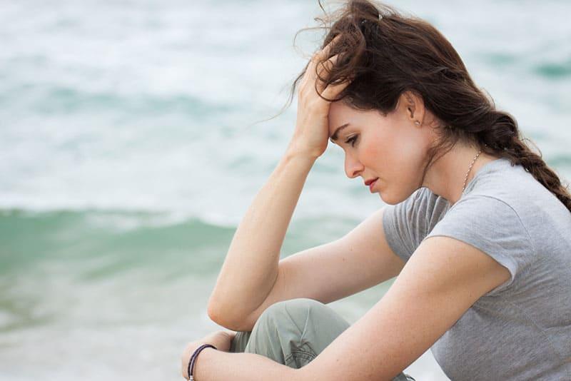 traurige Frau, die am Meer sitzt