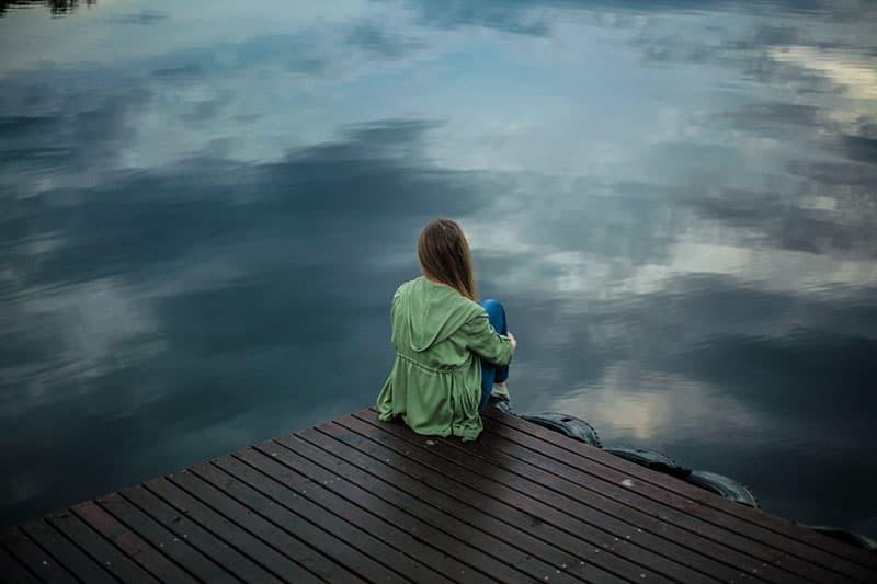 traurige Frau, die am See sitzt