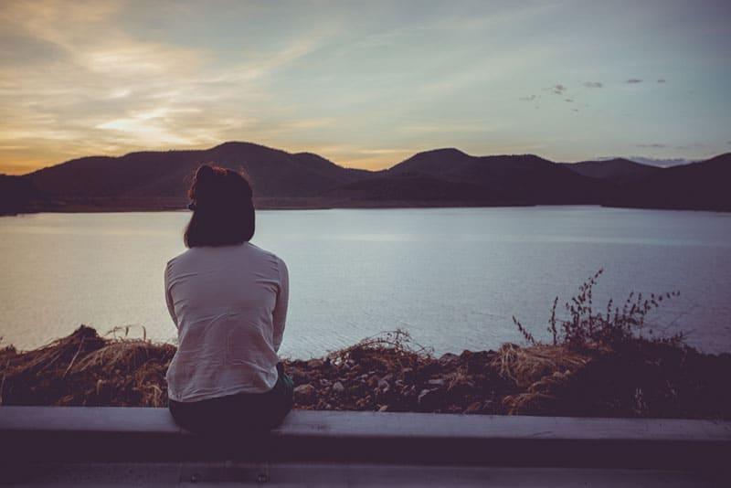 traurige Frau, die an der Wand am See sitzt