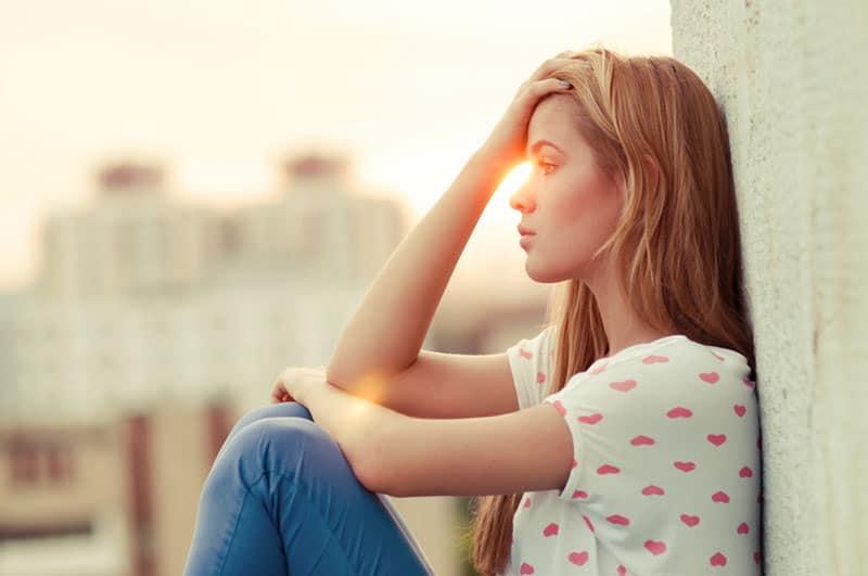 traurige Frau, die auf dem Dach an der Wand sitzt