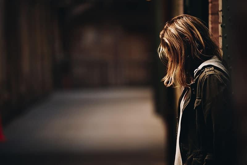traurige Frau, die draußen steht
