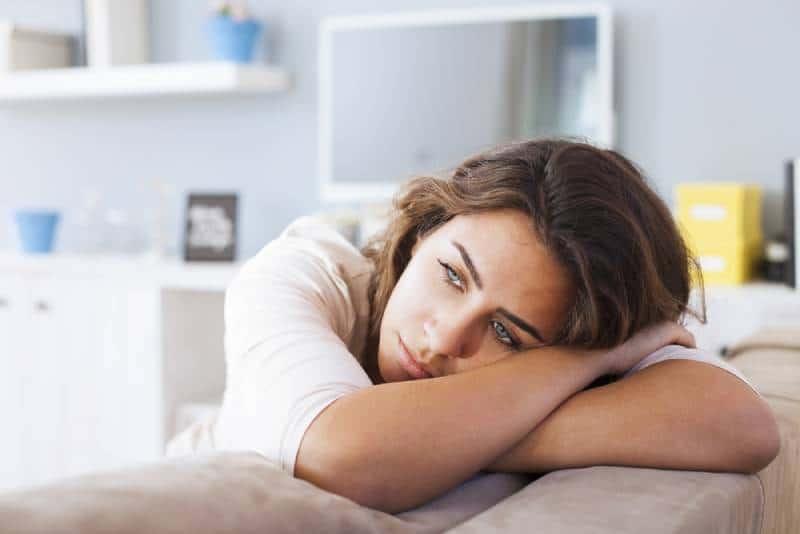 traurige Frau, die ihren Kopf auf Sofa legt und nachdenkt