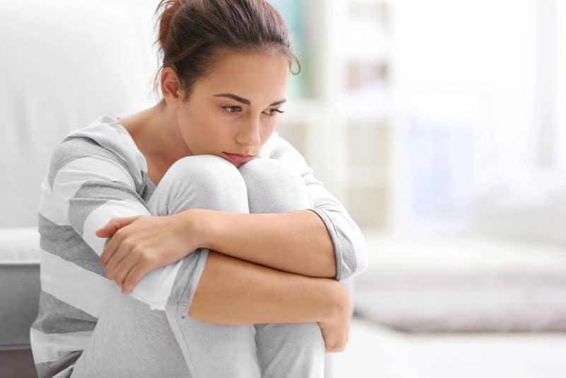 traurige achtsame Frau, die Boden betrachtet