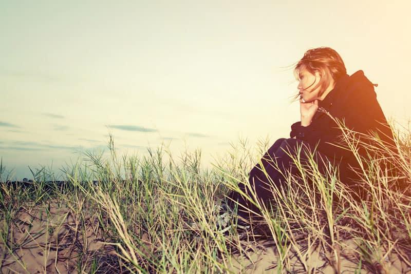 traurige achtsame Frau, die im Gras sitzt