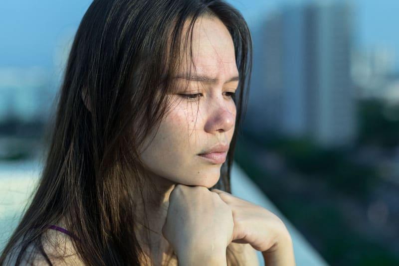 traurige asiatische Frau, die draußen steht