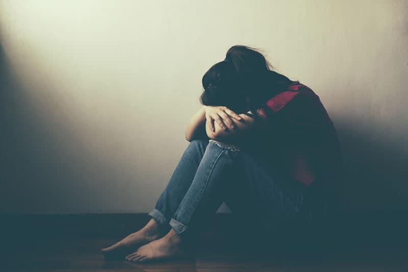 traurige depressive Frau, die auf dem Boden sitzt