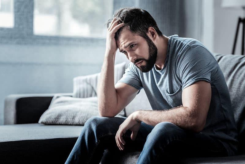 trauriger Mann, der im Wohnzimmer auf der Couch sitzt