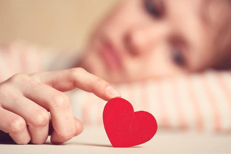 trauriges Mädchen, das Symbol des Herzens berührt